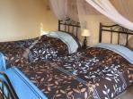 Spacious bedroom with air conditioning, 2 single beds and storage.