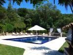 Private beach-club style pool terrace: sun beds, pizza oven, in-pool seating, and shaded sofa area