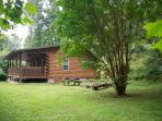 A side veiw of the cabin with the fire pit and picinic table