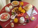 Breakfast consists of homemade bread, jams, cereals, yoghurts, orange juice, fruit platter,  & eggs.