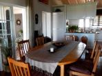 Dining table with 6-8 chairs, separated from the kitchen (in the back) by a counter