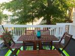 Deck off of kitchen with outdoor seating for 6 and five-burner gas grill.