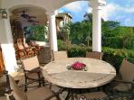 Enjoy alfresco dining on the Main House veranda above the pool terrace.