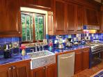 The Coco de Mer kitchen sparkles with its mahogany cabinetry, Italian tile, and Farmhouse sink.