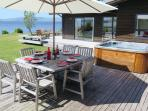 Sweeping deck with seating for 12 guests, spa and BBQ facilities