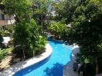 After lots of sunshine, the pool view is lush and green. Plenty of teak loungers for poolside.