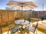 Enclosed patio with garden table, chairs and parasol