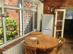 Dining table and chairs in conservatory with fridge/freezer.