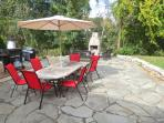 The large stone patio includes dining and an outdoor fireplace and is just off the covered walkway