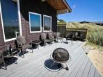 Large ocean facing deck with ample patio chairs, portable fire pit and hot tub.