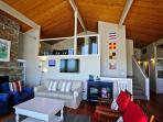 Living room with floor to ceiling picture with providing spectacular ocean views, wall mounted flat screen cable...