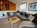 Upper level living room with TV/DVD, glass front wood stove, large sectional couch, two arm chairs and large picture...