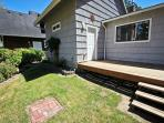Grassy backyard with large deck, charcoal BBQ and deck furniture