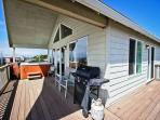 Large upper level ocean facing wrap around deck with an ocean view hot tub, deck chairs, gas BBQ and two sliders into ...