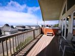 Large upper level ocean facing wrap around deck with an ocean view hot tub, deck chairs, gas BBQ and two sliders into...