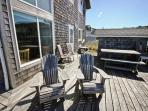 Large wrap around ocean facing deck with picnic table, charcoal BBQ, and deck furniture.