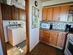 Fully equipped kitchen with all appliances and access to laundry area.
