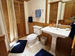Hall bathroom with a tile shower stall and pedestal sink.