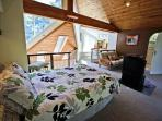 Upper level left bedroom that overlooks the living area with a Queen bed, cable TV/DVD, futon, walk-in closet and an ...