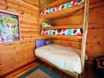Outside bunk house with a twin/double bunk bed, wall mounted TV/DVD and sink area.