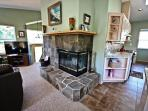Upper level open living room with a large flat screen TV/DVD, beautiful stone double sided wood fireplace, leather...