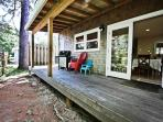 Side deck with patio chairs and gas BBQ.