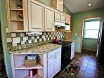 Fully equipped kitchen with stainless steel appliances and breakfast bar for two.