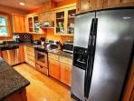 Fully equipped kitchen with stainless steel appliances and a breakfast bar for two.