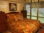 Main floor queen bed and view to ocean through glass louver windows.  Tropical ceiling fan overhead
