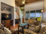 Living area with TV showing into the kitchen and out to the Lanai