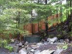Hot Tub under Alders with small waterfall running by it.