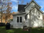 View of back of house, including deck, in fall.