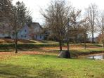 View of house from edge of pond in fall