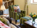 Easy chairs, thick rugs, throws & cushions make for a very cosy stay...