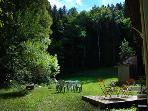 Le jardin avec meubles de terrasse et barbecue, entre forêt et rivière