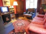 The red sitting room with TV and welcoming electric fire.
