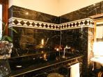 grande bagno in marmo con locale doccia e vasca