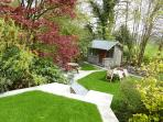 A beautifully terraced cottage garden with picnic table and benches