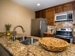 Gourmet kitchen with stainless steel appliances, refrigerator with ice maker, washer/dryer, pantry.
