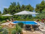 Holiday villa with pool and sundeck looking at the pine forest and the sea