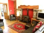 Lounge with oil burner in inglenook fireplace