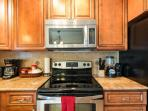 Kitchen has stainless steel flat top stove and microwave