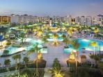 The Main Pool lit at night, it has a water park, and is over 5200 Sqft. A Grill and Activities