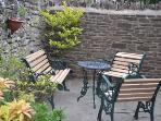 Private stoned walled patio with Welsh oak garden furniture.