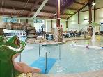 Indoor pool with slides, waterfall, and kiddie splash area