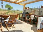 Large pergola covers the beautiful dining area and outside kitchen.