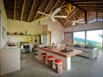 Open-plan kitchen (with NEW teak benches, pictured in next photo) comfy living area with sea views