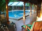 Cedar wooden pillars, mango and royal palm trees and tropical plants surround the pool's terraces