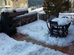 Detalle de la chimenea-barbacoa y la mesa exterior tras una nevada.