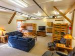 Living room is a large multi-sleeping room with 2 sets of extra long twin bunks, and two queen sofas